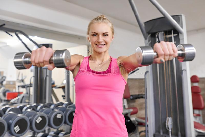 健身房的年轻运动的白肤金发的妇女 拿着金属重量的妇女 人健身体育健康生活方式概念 库存图片