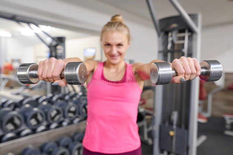 健身房的年轻运动的白肤金发的妇女 拿着金属重量,在kettlebells的焦点的妇女 人健身体育健康生活方式 免版税库存照片