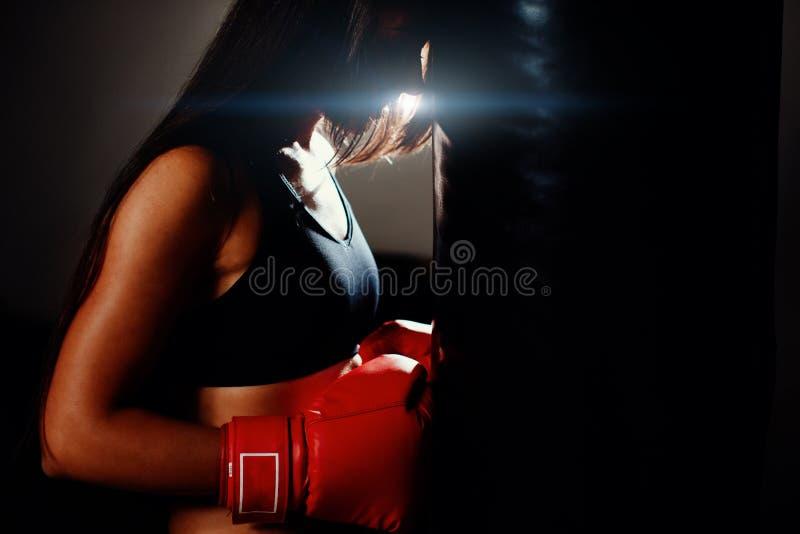 健身房的性感的战斗机女孩与拳击袋子 免版税库存照片