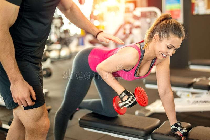 健身房的美丽的妇女与个人教练员 库存照片