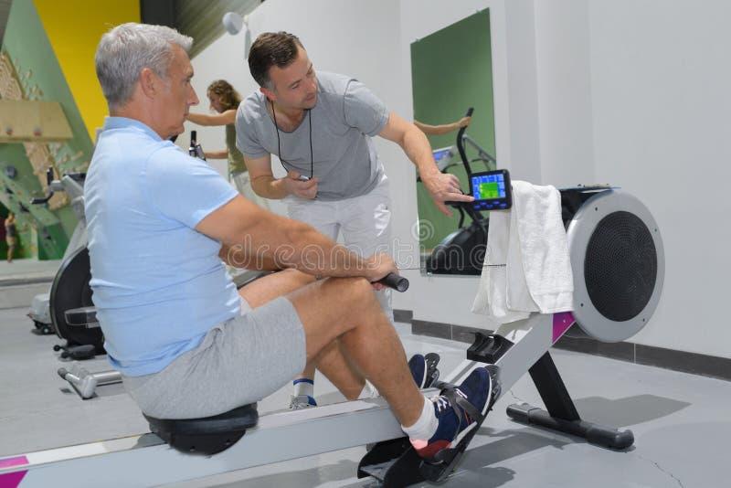 健身房的老人使用划船器 免版税库存照片