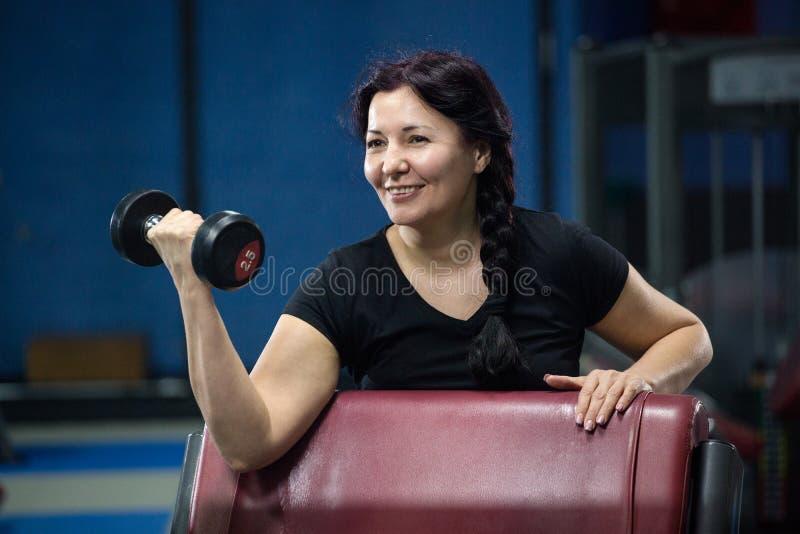 健身房的资深妇女解决与哑铃的 r r 免版税库存照片