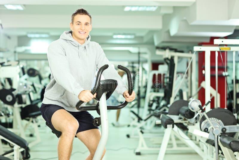 健身房的年轻微笑的人,行使他的做训练的腿 库存照片