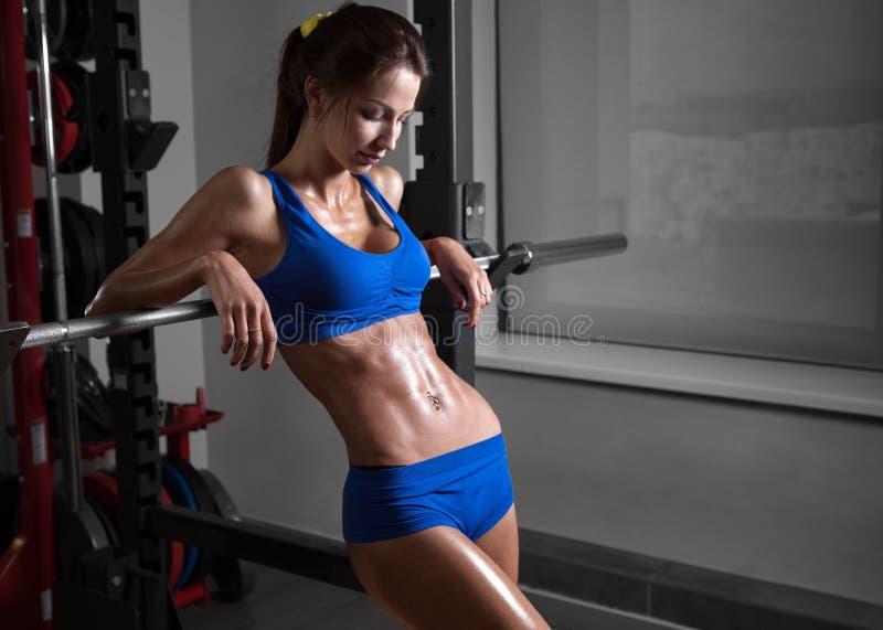 健身房的年轻美丽的运动员妇女 免版税库存照片