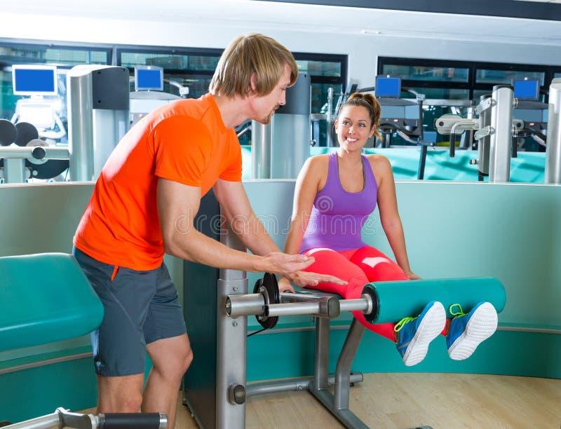 健身房腿引伸锻炼妇女个人教练员 免版税图库摄影