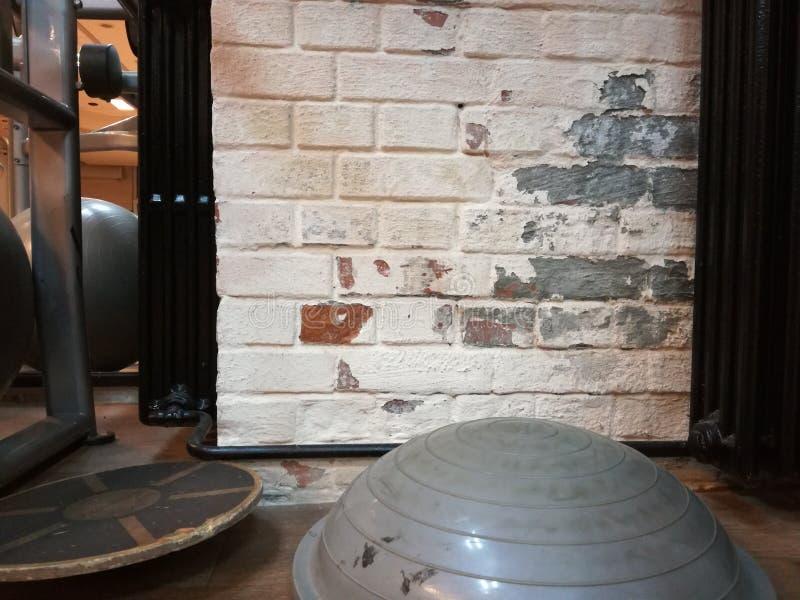 健身房被剥皮的墙壁镇压的普拉提 库存图片