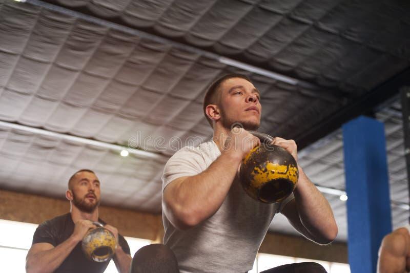 健身房训练的年轻人与Kettlebells 图库摄影