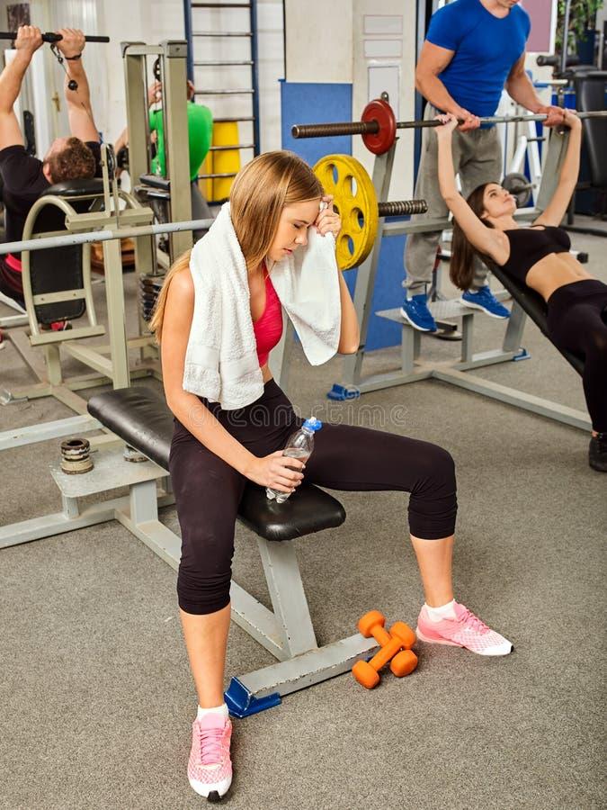 健身房锻炼健身设备的妇女 女孩饮料瓶装水 库存照片