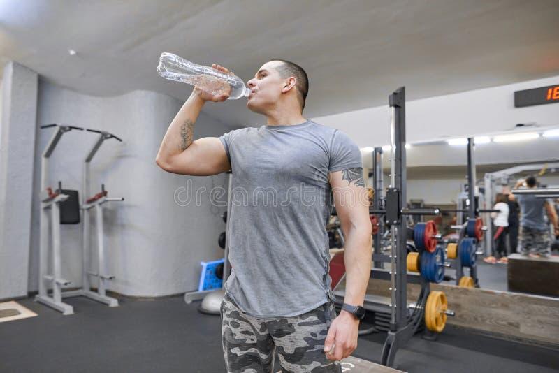 健身房饮用水的年轻坚强的肌肉人从瓶 免版税库存图片