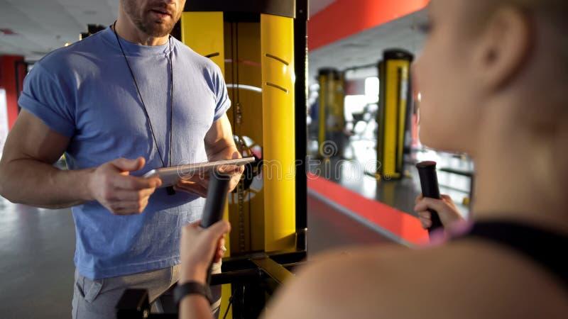 健身教练员谈话与少妇健身房,谈论训练计划,忠告 库存照片