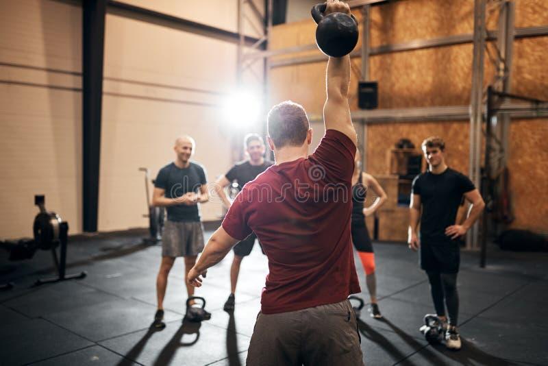 健身教练在健身房给人们演示锻炼 图库摄影