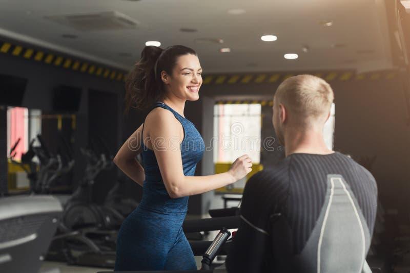 健身教练帮助省略教练员的妇女 库存图片