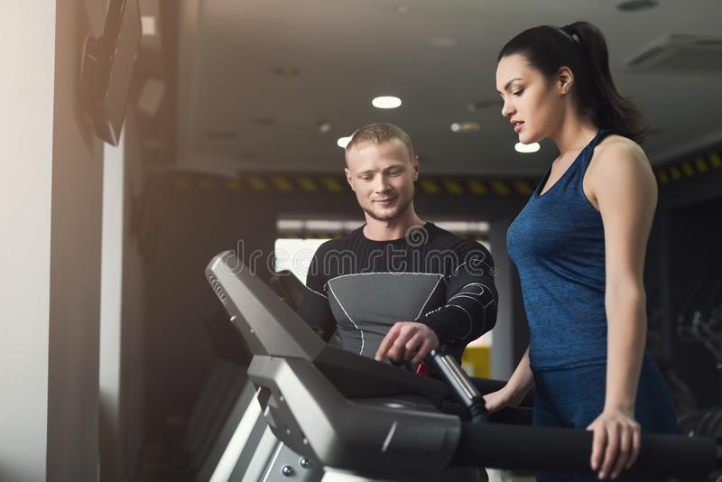 健身教练帮助省略教练员的妇女 免版税库存照片