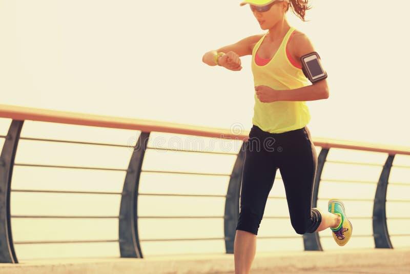 健身检查她的从巧妙的手表的妇女赛跑者运行时间在海边 库存图片