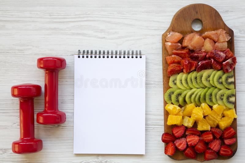 健身概念,饮食计划 切好的果子,哑铃,在白色木背景的笔记薄, 图库摄影