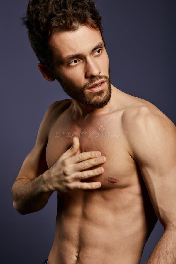 健身模型用在他的摆在照相机的乳房的手 库存照片