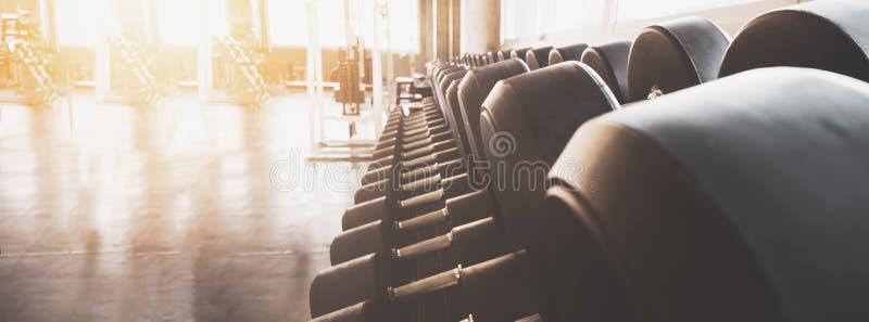 健身横幅背景关闭的健身房设备宽内部健身房哑铃和被弄脏的设备 免版税库存照片
