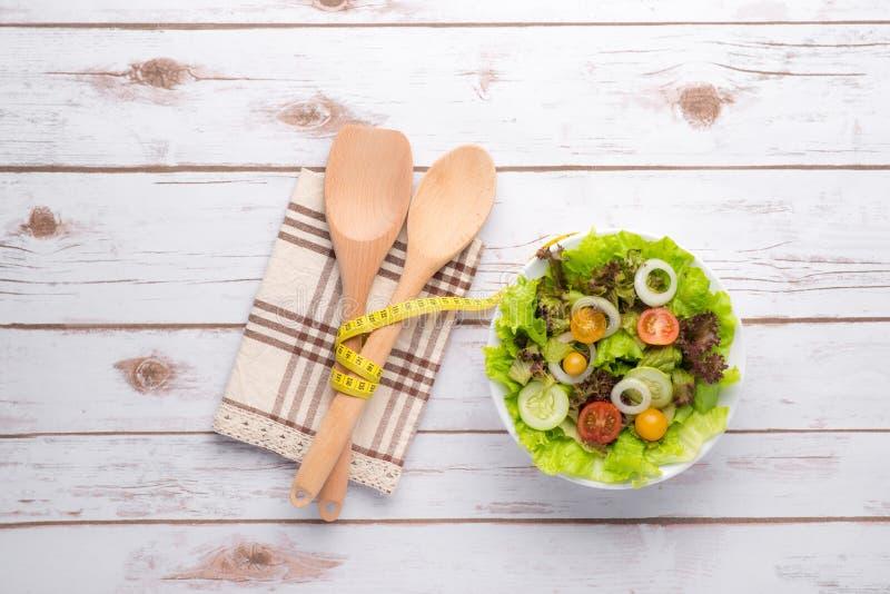 健身沙拉和测量的磁带在木桌上 免版税图库摄影
