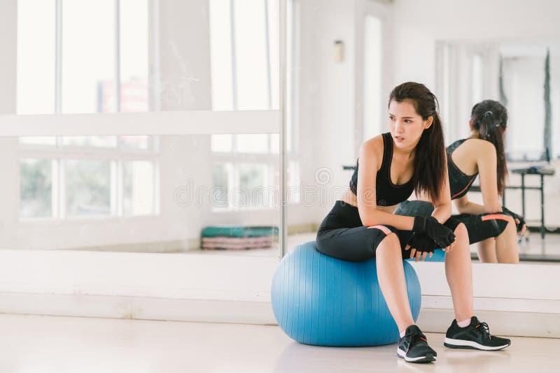 健身球的年轻和坚定的性感的亚裔女孩在与拷贝空间、体育和健康生活方式概念的健身房 免版税库存图片