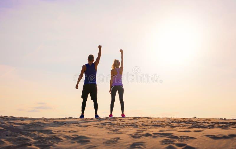健身男人和妇女有胳膊的庆祝体育目标 库存图片