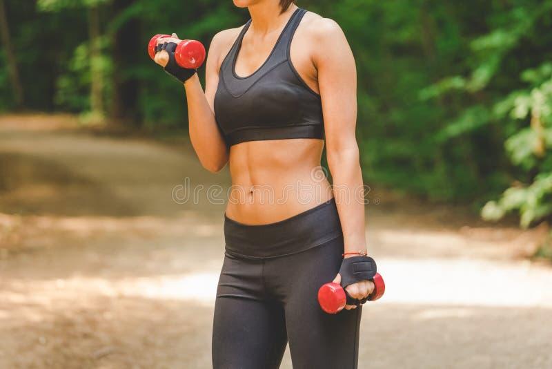 健身穿戴的年轻女性行使与重量的室外 库存图片