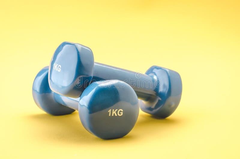 健身类/蓝色哑铃的设备在黄色背景 库存图片