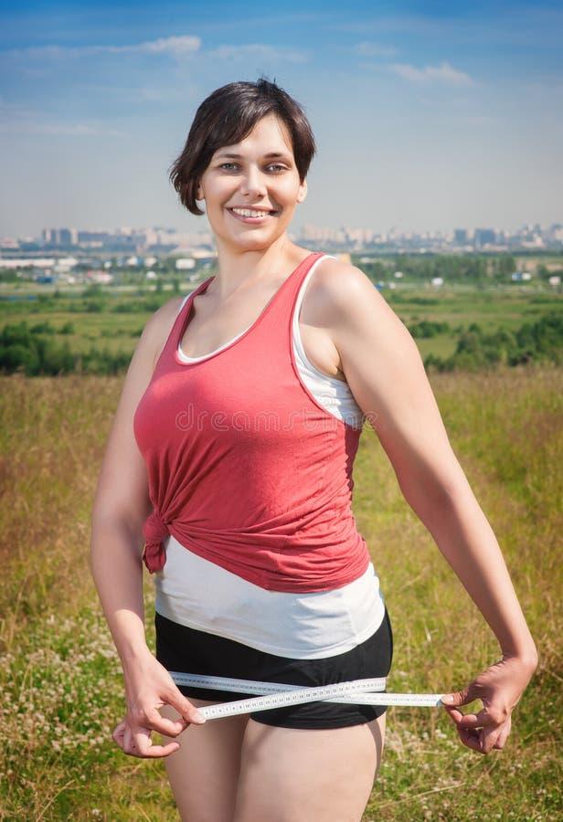 健身美好加上有卷尺的大小妇女 免版税库存图片
