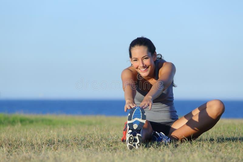 健身舒展在草的赛跑者妇女 免版税库存图片