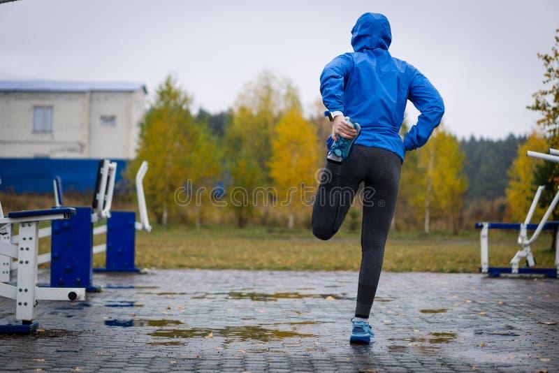 健身舒展腿的妇女赛跑者在奔跑前 适合健康 免版税库存照片