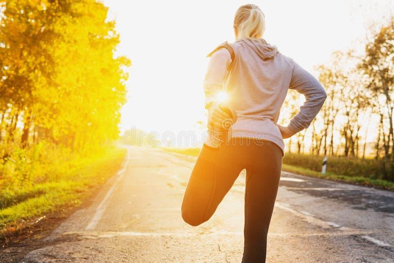 健身舒展腿的妇女赛跑者在路的奔跑前 免版税库存图片