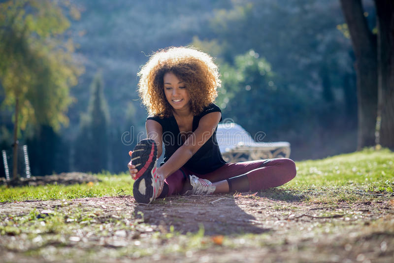健身舒展腿的黑人妇女赛跑者在奔跑以后 免版税图库摄影