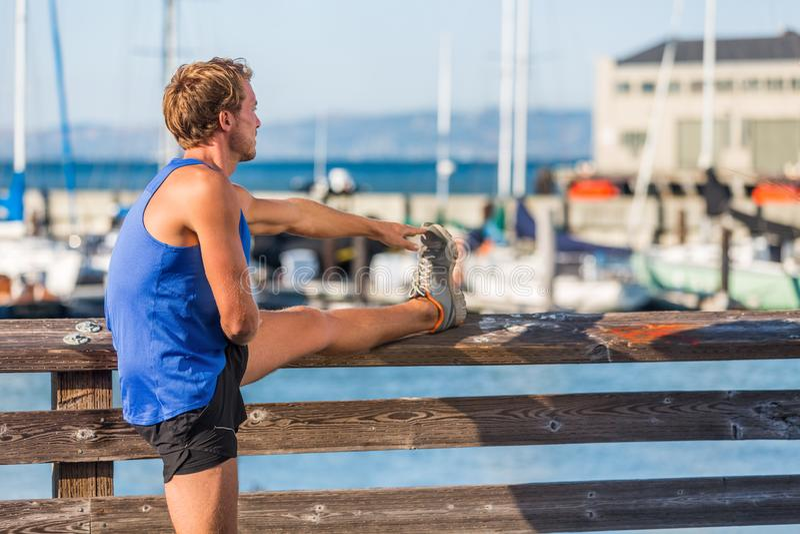 健身舒展腿肌肉的人赛跑者在连续锻炼在旧金山湾港口-城市生活方式前 运动员男性 免版税库存照片