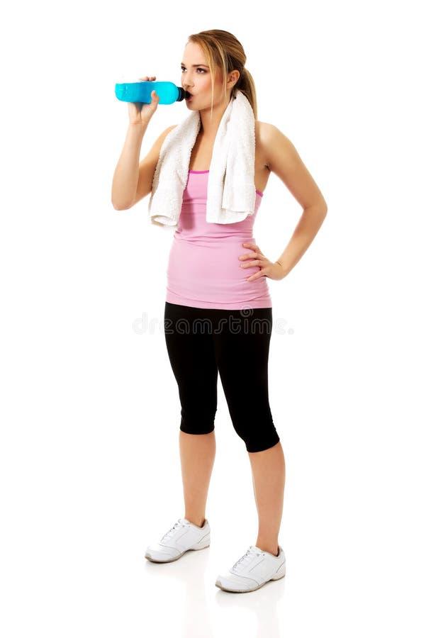 健身衣裳的妇女喝能量饮料的 免版税库存照片