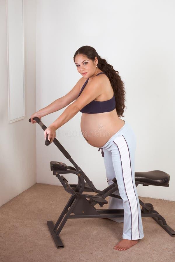 健身讲西班牙语的美国人孕妇工作 免版税库存照片