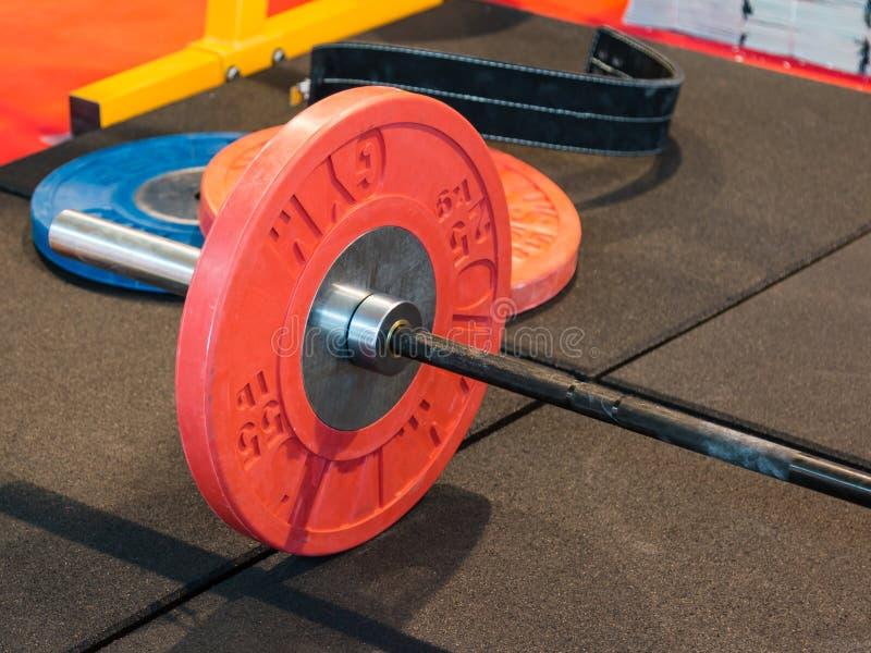 健身设备特写镜头在健身房的:与板材的杠铃 库存照片
