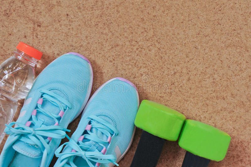 健身设备:运动鞋、哑铃和瓶在木背景的水 免版税库存照片