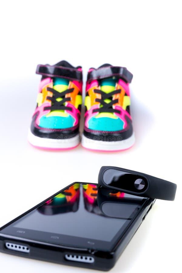 健身跟踪仪和智能手机在多色运动鞋附近 查出 库存图片
