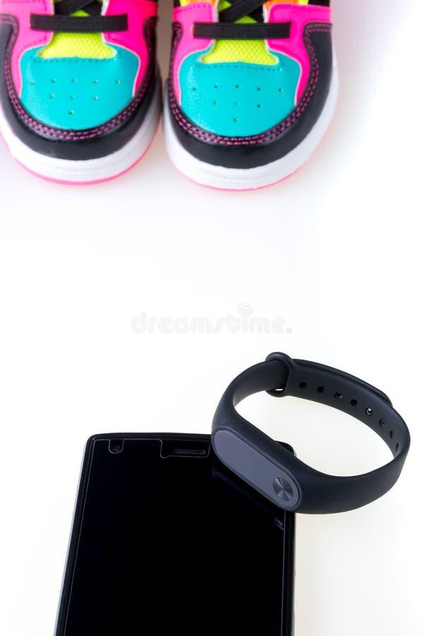 黑健身跟踪仪和智能手机在白色背景隔绝的多色运动鞋附近 库存照片