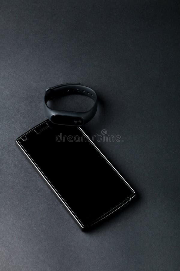 健身跟踪仪和智能手机在黑背景 炫耀镯子 库存照片