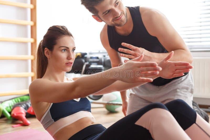 健身辅导员和妇女 免版税库存照片
