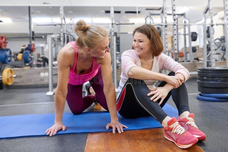 健身辅导员和成熟妇女健身房的 女性体育辅导员和中年妇女谈的微笑和笑在健康 免版税库存图片