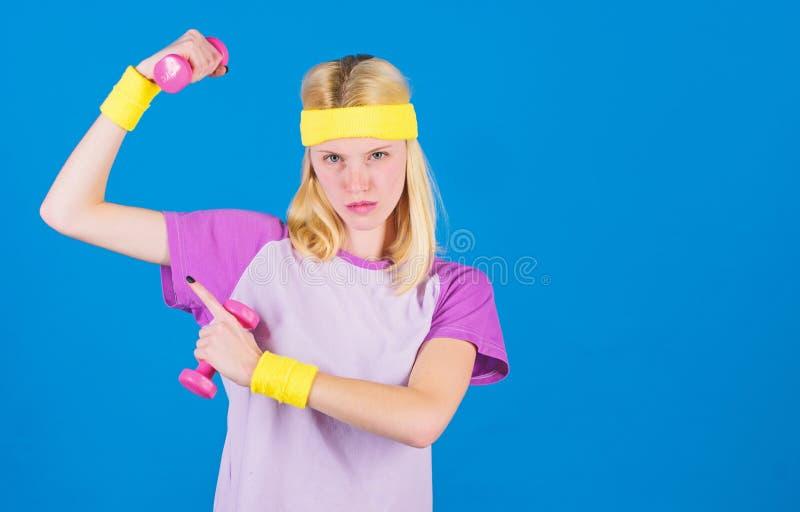 健身辅导员拿着一点哑铃蓝色背景 如何得到被定调子的体质 初学者健身锻炼 ?? 免版税库存图片