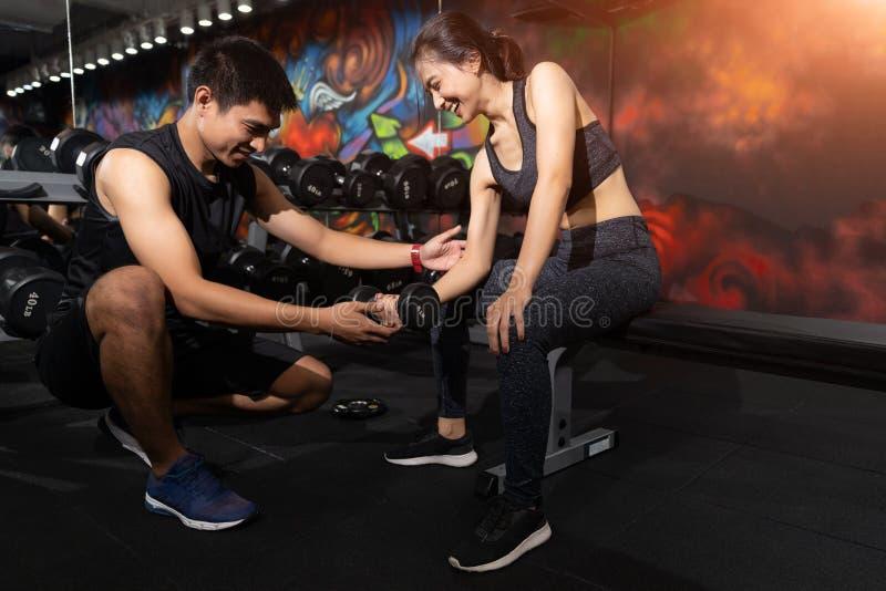 健身辅导员行使与他的客户的在健身房,个人教练员帮助的妇女与重的哑铃一起使用 库存照片