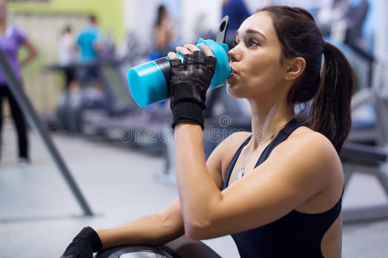 健身运动员妇女饮用水以后 免版税库存照片