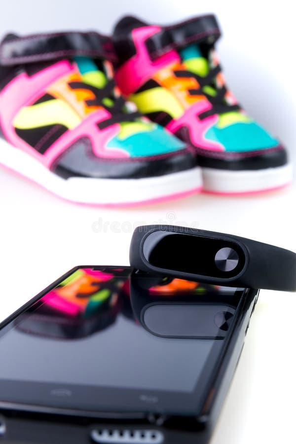健身镯子和智能手机在多色体育运动鞋附近 查出 库存图片