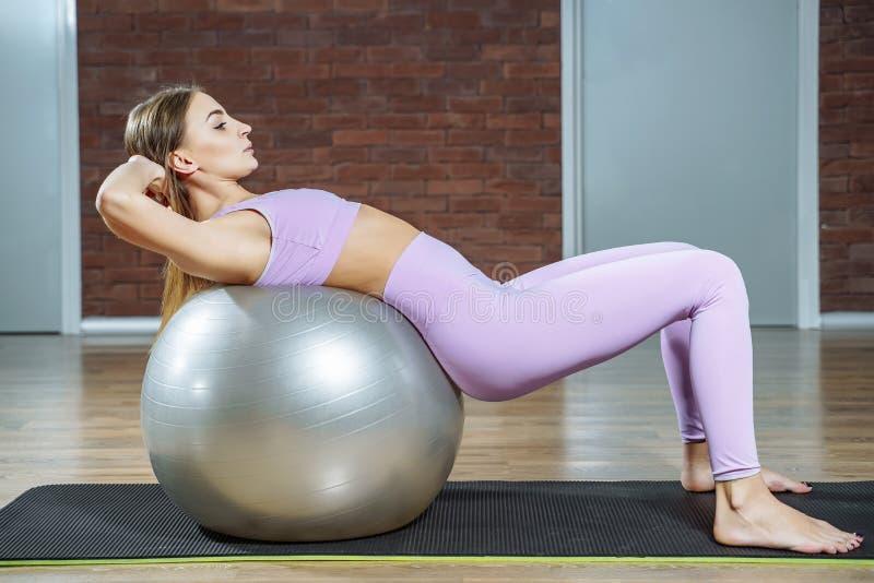 健身,体育,生活方式-做与适合的球的年轻女人锻炼在pilates类 免版税图库摄影