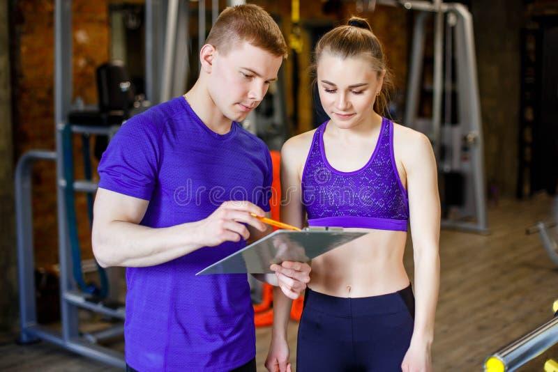 健身,体育,行使和饮食概念-妇女和个人教练员与剪贴板文字行使计划在健身房 库存照片