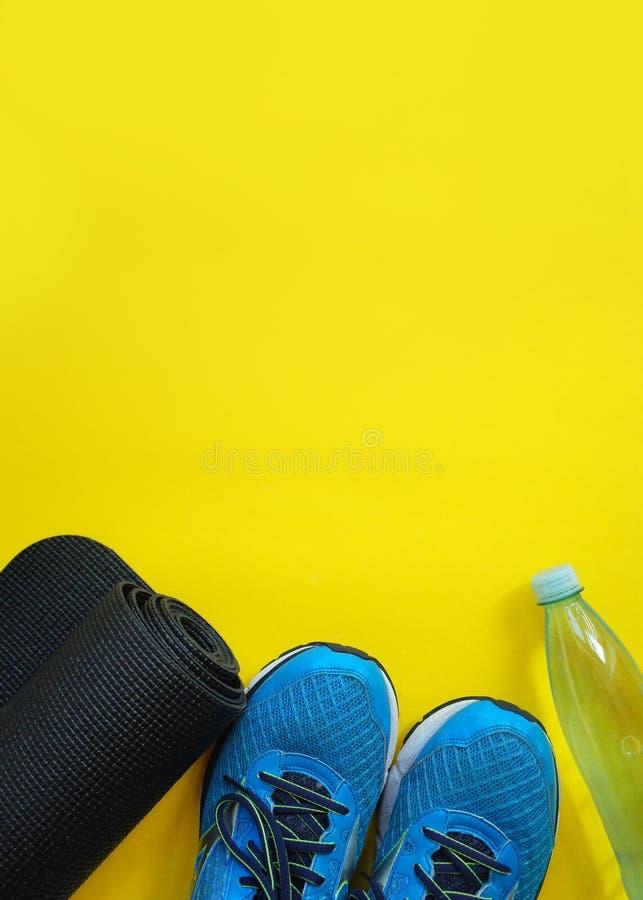健身,健康和活跃生活方式概念,运动鞋,瓶水,在黄色背景的席子 复制文本的空间 库存图片