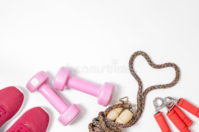 健身,健康和活跃生活方式爱概念、哑铃、运动鞋和跳绳在心形在白色背景 顶层 免版税库存图片