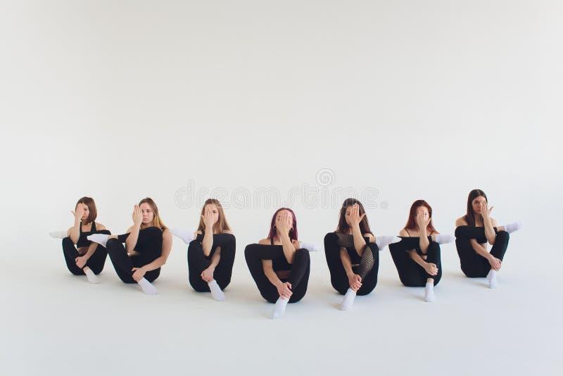 健身,舒展实践,解决在体育俱乐部的小组两名可爱的愉快的微笑的适合成熟妇女,做 免版税库存照片